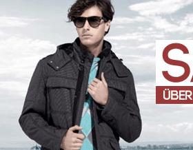 Oboy Gutschein (Mode-Gutschein) im Wert von 25 Euro - Ein Mann, der ein Zeichen hält, das für die Kamera aufwirft - Sonnenbrille