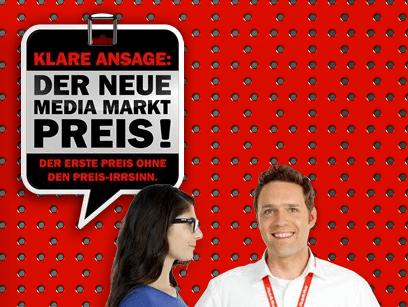 """Media Markt – """"Klare Ansage: Der erste Preis ohne den Preis-Irrsinn."""" - Eine Person, die ein Zeichen hält, das für die Kamera aufwirft - Media Markt"""